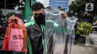 Driver Grab Bike menunjukkan Grab Protect pelindung yang membatasi antara pengemudi dan penumpang saat diluncurkan di Jakarta, Selasa (9/6/2020). Penumpang ojek online (ojol) kini tak perlu khawatir menggunakan transportasi ini di tengah pandemi Corona. (Liputan6.com/Faizal Fanani)