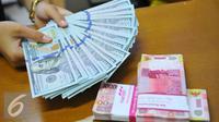Petugas menunjukkan mata uang dolar dan mata uang rupiah di penukaran uang di Jakarta, Rabu (9/11). Nilai tukar rupiah terhadap dolar Amerika Serikat (AS) pada saat jeda siang ini kian terpuruk di zona merah. (Liputan6.com/Angga Yuniar)