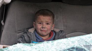 Seorang bocah menangis saat dievakuasi setelah serangan udara rezim di Kota Ariha, Idlib, Suriah, Rabu (15/1/2020). Sebanyak sembilan orang dilaporkan tewas dalam serangan pasukan pemerintah terhadap benteng terakhir oposisi tersebut. (Abdulaziz KETAZ/AFP)