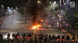 Polisi menembakan petasan dan gas air mata ke kerumunan massa di kawasan Pejompongan, Jakarta, Senin (30/9/2019). Demonstrasi menolak UU KPK hasil revisi dan RUU KUHP di depan Gedung DPR/MPR berakhir ricuh. (Liputan6.com/JohanTallo)