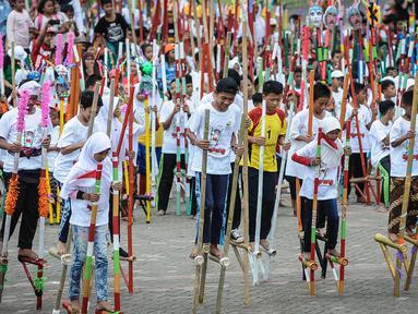 Sejumlah anak SD dan SMP meramaikan pemecahan rekor dunia egrang yang termasuk dalam rangkaian penyelenggaraan TAFISA World Games 2016 di Kemayoran, Jakarta, Sabtu (8/10). Pemecahan rekor Guinness Book itu diikuti 2.016 anak. (Liputan6.com/Faizal Fanani)