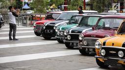 Pengunjung mengmbil gambar mobil Mini klasik pada Indonesia Mini Day 2018 di QBig BSD, Tangerang, Sabtu (15/12). Kegiatan tahunan dari berbagai komunitas ditujukan untuk mempererat silaturahmi. (Liputan6.com/Fery Pradolo)