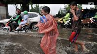 Anak-anak penjual jas hujan dan ojek payung bermain air saat banjir menggenangi Jalan DI Panjaitan, Jakarta, Senin (3/12).  Menurut petugas, banjir disebabkan oleh buruknya sistem drainase atau gorong-gorong. (Merdeka.com/ Iqbal S. Nugroho)