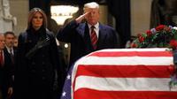 Presiden AS Donald Trump dan Melania Trump memberikan penghormatan terakhir kepada George HW Bush di Gedung Capitol, Washington, Senin (3/12). Jenazah Presiden ke-41 AS itu disemayamkan di Rotunda Capitol Hill selama beberapa hari. (AP/Patrick Semansky)