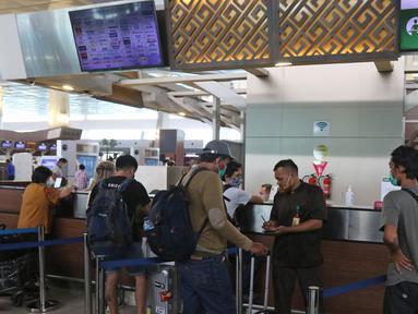 Calon penumpang mengantre di pelayanan tiket di Terminal 3 Bandara Soekarno Hatta, Tangerang, Banten, Selasa (10/11/2020). Maskapai penerbangan Garuda Indonesia dan Citylink melakukan penyesuaian beberapa jadwal penerbangan. (Liputan6.com/Herman Zakharia)
