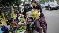Seorang wanita usai membeli kulit ketupat di Pasar Palmerah, Jakarta, Senin (2/6/2019). Peningkatan drastis dikarenakan banyak warga yang ingin membuat masakan khas Lebaran seperti Opor Ayam yang selalu ditemani ketupat sebagai pengganti lontong. (Liputan6.com/Faizal Fanai)