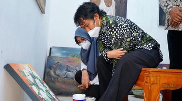 Lukman Hakim (29), pelukis difabel asal Desa Singolatren, Kecamatan Singojuruh, Kabupaten Banyuwangi. (Dian Kurniawan/Liputan6.com)