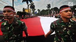 Anggota TNI POLRI  membawa bendera raksasa saat gelaran Festival Merah-Putih (FMP) 2018 di kawasan Air Mancur, Bogor,  Minggu (5/8). Bendera tersebut berukuran panjang 117 meter dan lebar 5 meter. (Merdeka.com/Arie Basuki)