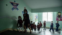 Anak-anak sekolah dasar dengan memakai masker tiba untuk mengikuti kelas di Sekolah Dasar Hasin di Distrik Sosong di Pyongyang, Rabu (3/6/2020). Korea Utara membuka kembali sekolah - sekolah di bulan ini setelah sebelumnya meliburkan karena kekhawatiran penyebaran virus corona. (KIM Won Jin / AFP)