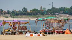 Kios-kios yang menjual bahan ibadah umat Hindu didirikan di Sungai Gangga, selama festival Gangga Dussehra, India (1/6/2020). Ratusan umat Hindu melakukan pencucian suci meskipun jemaat di tempat-tempat keagamaan terus dilarang selama penguncian coronavirus nasional. (AP Photo/Rajesh Kumar Singh)
