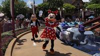 Karakter Minnie dan Mickey Mouse melambai kepada pengunjung di Disneyland Hong Kong, Kamis (18/6/2020). Disneyland Hong Kong kembali beroperasi pada 18 Juni 2020 dengan menerapkan sejumlah protokol kesehatan baru untuk mencegah penyebaran COVID-19. (AP Photo/Kin Cheung)