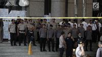 Petugas kepolisian memasang garis polisi di sekitar lokasi Gedung BEI, Jakarta, Senin (15/1). Demi keamanan dan keselamatan, pihak keamanan menutup area sekitar lokasi gedung BEI yang ambruk. (Liputan6.com/Arya Manggala)