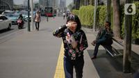 Seorang wanita menutupi wajahnya selama gelombang panas di Jakarta, Selasa (22/10/2019).  BMKG memprediksi wilayah Indonesia akan mengalami panas selama kurang lebih satu minggu ini. Hal ini dikarenakan matahari yang berada dekat dengan jalur khatulistiwa. (Liputan6.com/Faizal Fanani)