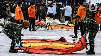 Prajurit TNI meletakan kantong jenazah korban pesawat Sriwijaya Air SJ-182 yang jatuh di perairan Pulau Seribu, di Dermaga JICT, Jakarta, Selasa (12/1/2021). Tim SAR kembali membawa secara berkala temuan korban dan puing pesawat Sriwijaya Air SJ 182. (Liputan6.com/Johan Tallo)