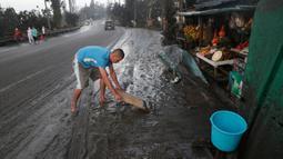 Warga membersihkan jalanan dari abu vulkanik setelah erupsi Gunung Taal di Tagaytay, Provinsi Cavite, Filipina, Senin (13/1/2020). Gunung yang terakhir meletus pada tahun 1977 tersebut melontarkan abu vulkanik mencapai 50.000 kaki (15.000 meter) ke atmosfer. (AP Photo/Aaron Favila)