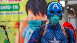 Seorang petugas kepolisian yang berpakaian superhero menyemprotkan cairan disinfektan di jalan kawasan Pasuruan, Jawa Timur, Kamis (9/4/2020). Penyemprotan cairan disinfektan tersebut bertujuan untuk mengantisipasi penyebaran Virus Corona (COVID-19). (JUNI KRISWANTO / AFP)