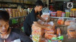 Pekerja menata dagangan kue kering di salah satu toko penjualan kue kering di kawasan Ciracas, Jakarta, Selasa (19/5/2020). Adanya pandemi covid-19 diakui para pedagang menyebabkan penjualan kue kering menjelang lebaran turun hingga 50 persen. (Liputan6.com/Immanuel Antonius)