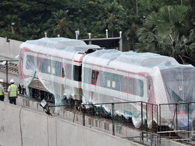 Aktivitas pekerja proyek pengerjaan Light Rail Transit (LRT) di Jalur Section 5A, Kelapa Gading, Jakarta Utara, Rabu (18/4). Dua gerbong kereta LRT buatan Hyundai Roterm diangkut ke Velodrome-Kelapa Gading sejak 15 April 2018. (Merdeka.com/Iqbal Nugroho)