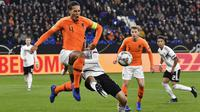 Bek Belanda, Virgil Van Dijk, berebut bola dengan penyerang Jerman, Thomas Mueller, pada laga UEFA Nations League di Veltins Arena, Gelsenkirchen, Senin (19/11/2018). Kedua tim bermain imbang 2-2. (AP/Martin Meissner)