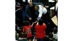 President Amerika Serikat Barack Obama menyalami penonton pada pembukaan NBA antara  Cleveland Cavaliers melawan Chicago Bulls di Chicago, Selasa(27/10/2015). (REUTERS / Jonathan Ernst)