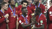 Penyerang Liverpool, Sadio Mane mencium trofi Piala Dunia Antarklub 2019 setelah mengalahkan Flamengo di Stadion Internasional Khalifa di Doha, Qatar (22/12/2019). Liverpool menang 1-0 atas Flamengo berkat gol tunggal Roberto Firmino di menit ke-99. (AP Photo/Hassan Ammar)