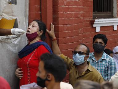 Seorang petugas kesehatan mengambil sampel usap untuk menguji COVID-19 di Prayagraj, India, Rabu (7/4/2021). India mencapai puncak baru dengan 115.736 kasus COVID-19 dalam 24 jam. (AP Photo/Rajesh Kumar Singh)