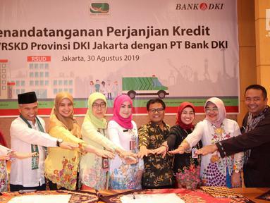 Direktur Kredit UMK & Usaha Syariah Bank DKI Babay Parid Wazdi (keempat kanan), Kadis Kesehatan DKI Jakarta Widyastuti dan 6 perwakilan RSUD DKI usai penandatanganan Persetujuan Kredit Modal Kerja Pinjaman Tetap Berjangkasenilai Rp93 miliar di Jakarta, Jumat (30/8/2019). (Liputan6.com/HO/Budi)