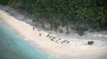 "Dua orang berdiri disamping tulisan ""Help"" yang tersusun dari dahan pohon palem di pulau tak berpenghuni Faradik, Mikronesia, 7 April 2016. Tiga orang pelaut berhasil diselamatkan pasukan AL Amerika Serikat setelah tiga hari terdampar. (AFP Photo)"