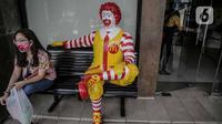 Seorang wanita duduk disamping patung Ronald di gerai makanan cepat saji McDonals's komplek pusat perbelanjaan Sarinah, Jakarta, Jumat (8/5/2020). Penutupan gerai ini dikarenakan pihak manajemen gedung sarinah akan merenovasi dan mengubah strategi bisnis. (Liputan6.com/Faizal Fanani)