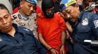 Polisi menggiring tersangka kasus pembunuhan pensiunan TNI AL Hunaedi di Jakarta, Kamis (12/4). Hunaedi dibunuh pada 5 April 2018 lalu. (Liputan6.com/Immanuel Antonius)
