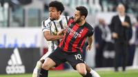 Gelandang AC Milan, Hakan Calhanoglu, menghalangi pergerakan pemain Juventus, Weston McKennie, pada laga Liga Italia di Stadion Allianz, Senin (10/5/2021). AC Milan menang dengan skor 3-0. (Tano Pecoraro/LaPresse via AP)