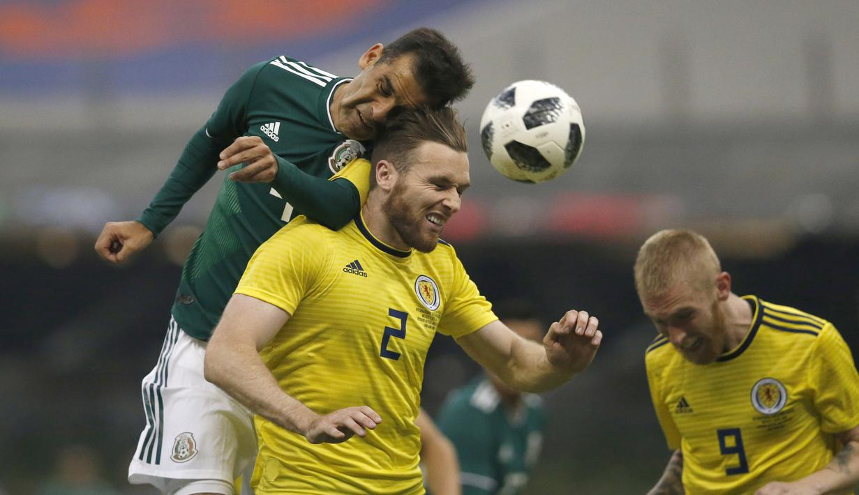 Duel pemain Meksiko, Rafael Marquez (kiri) dengan pemain Skotlandia, Stephen O'Donnell (tengah) pada laga uji coba di Azteca Stadium, Meksiko City, (2/6/2018). Meksiko menang 1-0. (AP/Rebecca Blackwell)