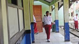 Arya Permana berjalan di SDN Cipurwasari 1 kawasan Karawang, Jawa Barat, Selasa (9/4). Arya Permana diketahui memiliki berat badan hingga 192 kg, sekarang sudah turun 105 kg menjadi 87 kg pasca operasi lambung. (Liputan6.com/Herman Zakharia)