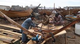 Tukang kayu Pakistan menyelesaikan pembuatan kapal penangkap ikan di sebuah pelabuhan di Karachi (3/4). Pembuatan kapal buatan Pakistan menghasilkan ratusan kapal setiap tahun untuk memenuhi permintaan industri perikanan setempat. (AFP Photo/Asif Hassan)