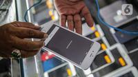 Petugas toko memeriksa IMEI handphone untuk didata di ITC Roxy Mas, Jakarta, Selasa (26/11/2019). Kemendag, Kemenperin, dan Kemenkominfo mulai memberlakukan aturan validasi IMEI pada 18 April 2020. (Liputan6.com/Faizal Fanani)