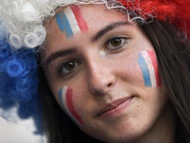 Suporter wanita melukis bendera Prancis di wajahnya sebelum menyaksikan pertandingan melawan Norwegia pada grup A Piala Dunia Wanita 2019 di Stadion Nice, Prancis (12/6/2019). Dalam pertandingan ini Prancis menang tipis atas Norwegia 2-1. (AFP Photo/Christophe Simon)