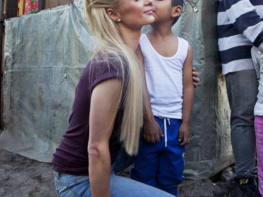 Aktris Paris Hilton dicium seorang anak saat mengunjungi keluarga yang terkena dampak gempa bumi pada September 2017 di San Gregorio Atlapulco, Meksiko (12/11). Paris Hilton tampil mengenakan kaos, jeans dan sepatu hitam. (AFP Photo/Antonio Nava)