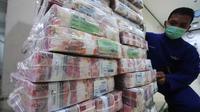 Petugas merapikan uang di Kantor Kas Bank Mandiri, Jakarta, Senin (4/1/2016). Nasib rupiah di tahun 2016 sulit menguat di tengah tingginya permintaan dollar. (Liputan6.com/Angga Yuniar)