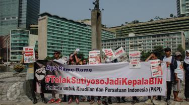 Aktivis Pemuda Untuk Keadilan dan Persatuan Indonesia (PKPI) menggelar aksi damai di Bundaran HI, Jakarta, Minggu (28/6/2015). Mereka menolak mantan Gubernur DKI Jakarta Sutiyoso menjadi Kepala Badan Intelijen Negara (BIN). (Liputan6.com/Faizal Fanani)