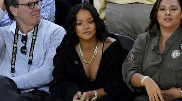 Penyanyi Rihanna saat menyaksikan pertandingan gim pertama Final NBA 2017 antara Golden State Warriors melawan Cleveland Cavaliers di Oracle Arena, Oakland, (1/6). Rihanna tampil dengan busana berwara hitam. (Thearon W. Henderson/Getty Images/AFP)