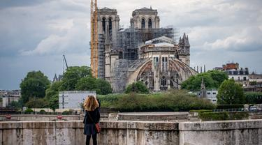 Seorang wanita mengamati Katedral Notre-Dame yang tengah dipugar di Paris, Prancis, Senin (27/4/2020). Renovasi Katedral Notre-Dame dilanjutkan kembali setelah sempat dihentikan sejak 17 Maret lalu akibat epidemi COVID-19. (Xinhua/Aurelien Morissard)