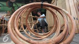 Pekerja rengah saat menguas kursi duduk rotan di Jakarta, Kamis (3/12). Usai pemberlakuan larangan ekspor rotan mentah, Perkumpulan Untuk Peningkatan Usaha Kecil (Pupuk) ingin menstabilkan harga yang kian turun. (Liputan6.com/Angga Yuniar)