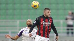 Pemain AC Milan, Ante Rebic, duel udara dengan pemain Fiorentina, Sofyan Amrabat, pada laga Liga Italia di Stadion San Siro, Minggu (29/11/2020). AC Milan menang dengan skor 2-0. (AP/Luca Bruno)
