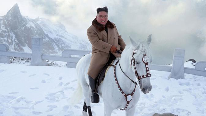 Pemimpin Korea Utara Kim Jong-un tersenyum saat berada di atas kuda putih saat salju turun di gunung Paektu (16/10/2019). Kim Jong-un tampil mengenakan kaca mata dengan mantel tebal berwarna coklat.  (Photo by STR/KCNA VIA KNS/AFP)