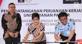 Kepala Kantor Imigrasi Kelas I Khusus Jakarta Barat, Lumaksono (kanan) Direktur Lippo Mall Puri, Rita Yovita (tengah) menandatangani MOU kerjasama pembukaan gerai layanan paspor pertama se-Indonesia di Jakarta, Selasa (16/10). (Merdeka.com/Arie Basuki)