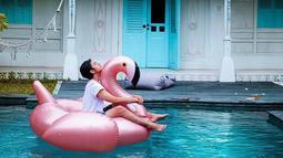 Duduk santai di atas giant float falminggo sembari nikmatin suasana, begini cara pemain film 'Sunyi' menghabiskan waktu di Lombok. Hanya dengan tshirt putih polos dan pants, gaya liburan Angga terlihat simple dan tetap memesona.(Liputan6.com/IG/@anggayunandareal16)