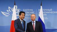Perdana Menteri Jepang (kiri) Shinzo Abe berjabat tangan dengan Presiden Rusia (kanan) Vladimir Putin (AFP)