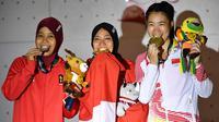 Peraih medali emas Indonesia Susanti Rahayu Aries (tengah), medali perak Indonesia Puji Lestari dan medali perunggu China, He Cuilian berpose pada upacara medali olahraga panjat tebing wanita Asian Games 2018 di Palembang (23/8). (AFP PHOTO / Adek Berry