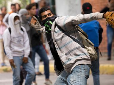 Mahasiswa Venezuela Central University melempar batu ke arah polisi selama protes menuntut peningkatan anggaran beasiswa dan membuka kembali kafetaria universitas di Caracas, Venezuela (21/11). (AP Photo/Ariana Cubillos)