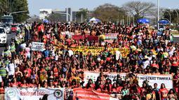 Perempuan pribumi berjalan kaki saat menggelar protes terkait kebijakan Presiden Brasil Jair Bolsonaro di Brasilia, Selasa (13/8/2019). Demonstrasi diikuti sekitar 3.000 perempuan pribumi dari seluruh Brasil. (EVARISTO SA/AFP)